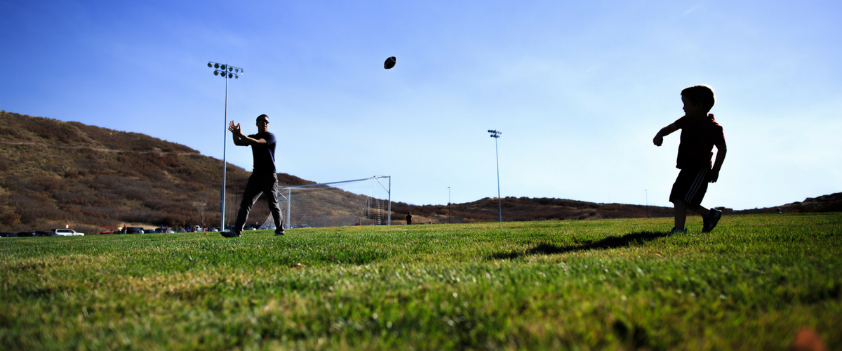 Dad and son play catch at synthetic-turf field at Philip S. Miller Park in Castle Rock